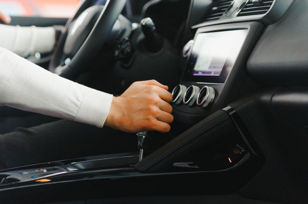 Hand on gear shift in car