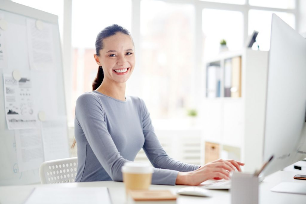 Woman smiling while typing on computer