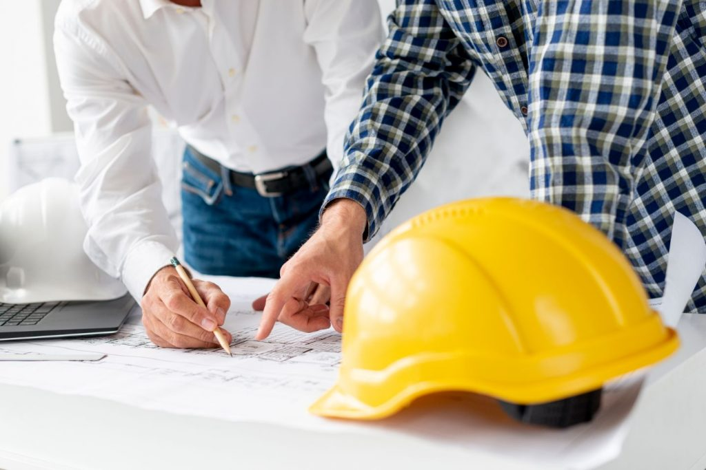 Hardhat in foreground, people pointing at paper in background